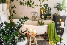 a boho chic bathroom with a vintage tub, some lights and candles, potted plants all around the tub and suspended