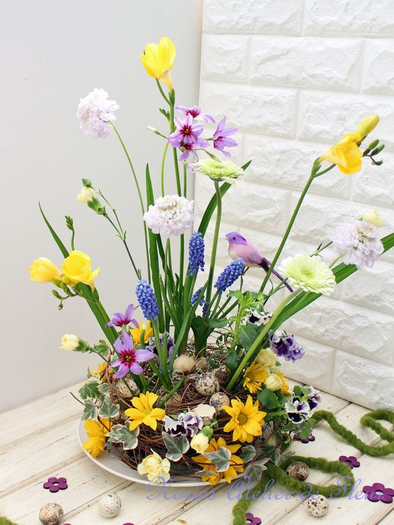 a bold Easter flower arrangement with a nest with speckled eggs, bright blooms and fake birds