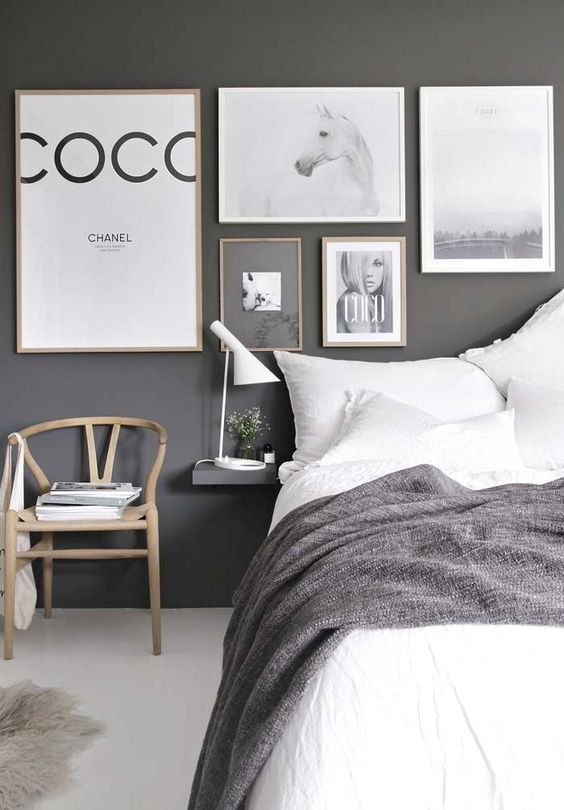 a bold monochromatic bedroom with a dark wall, lots of artworks, a comfy bed, a chair and floating nightstands