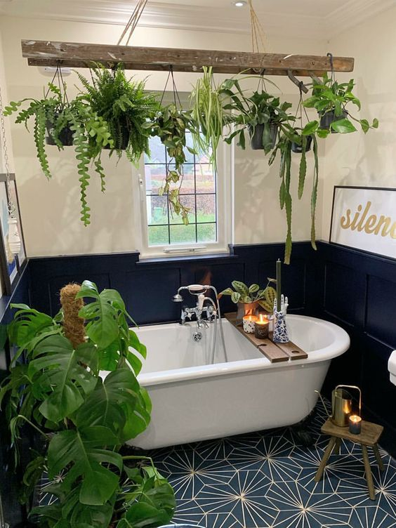 a bold navy and neutral bathroom with a tile floor, paneling and lots of potted green plants around the tub