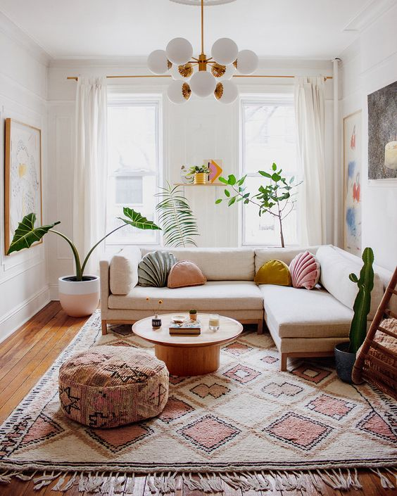 a bright and chic modern living room with a neutral sofa, a boho rug and ottoman, pastel pillows and potted plants