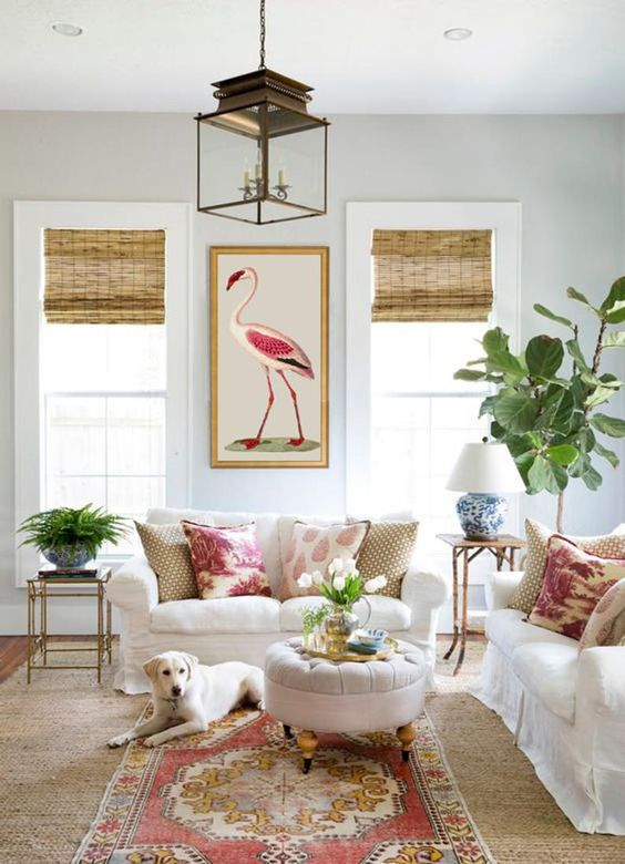 a bright and cool living room with white furniture, greenery and neutral blooms, a boho rug and printed curtains, a bold artwork