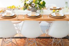 a bright and fresh spring table setting with a yellow and spring floral centerpiece, wicker chargers, a white runner and yellow napkins