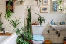 a bright blue and white bathroom with lots of greenery in various pots here and there feels alive