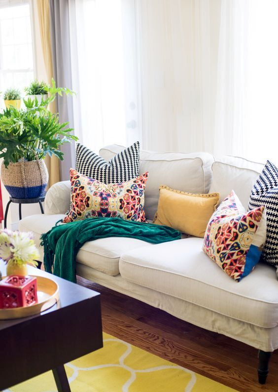 a bright living room with a white sofa accented with bright pillows, a bold rug and a dark coffee table plus greenery