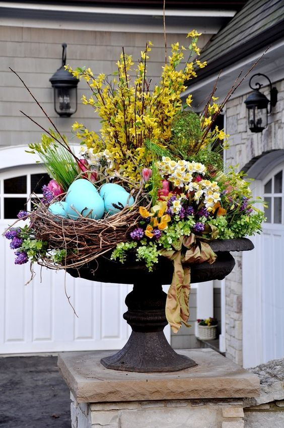 a bright outdoor Easter arrangement with yellow, purple, pink blooms, greenery and large fake blue eggs