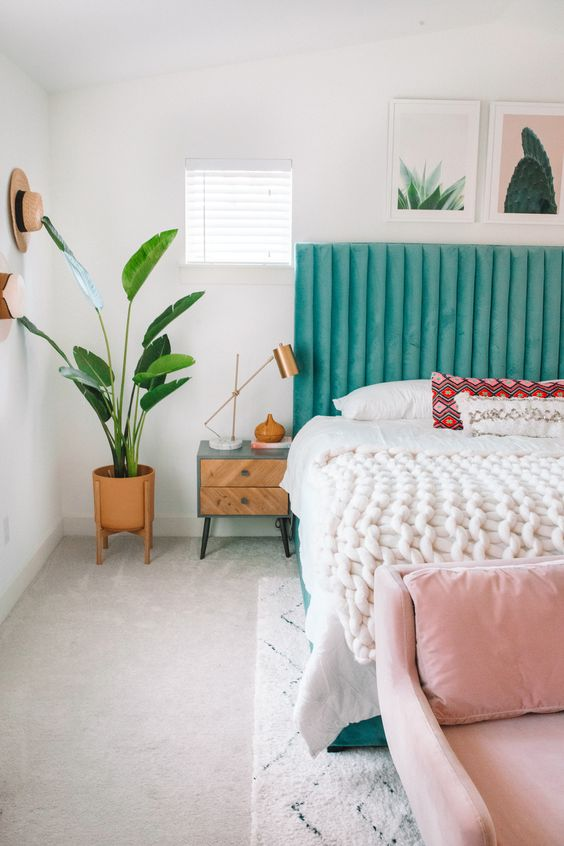 a bright spring bedroom with a turquoise bed, a pink bench, potted greenery and artworks already feels like spring itself