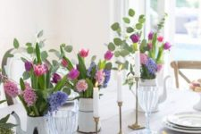a bright spring table setting with colorful floral centerpieces, gilded touches and an uncovered table
