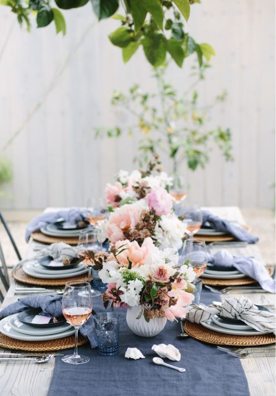 a bright spring table setting with navy napkins and a table runner, wicker chargers and blue porcelain and pink and white floral centerpieces