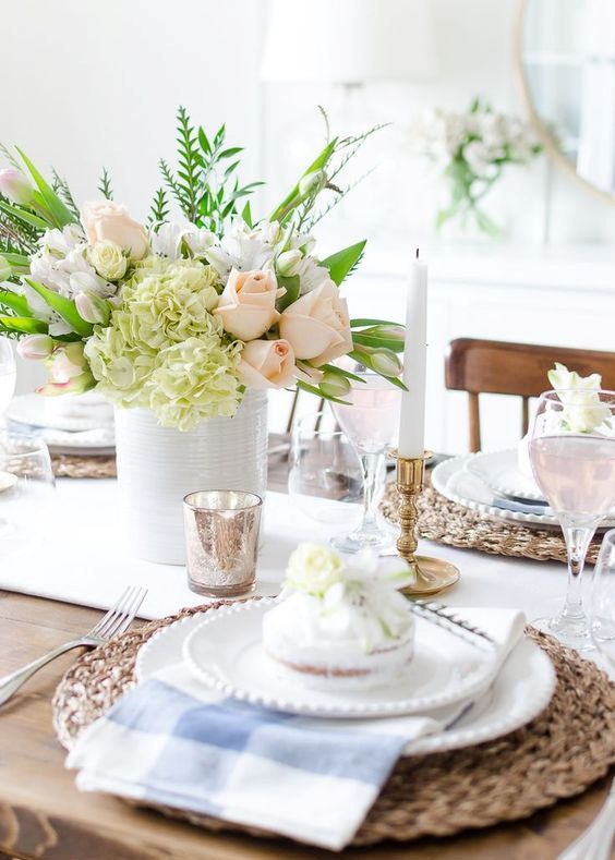 a bright spring tablescape with wicker chargers, checked napkins, a pastel floral centerpiece and some mercury glass accessories