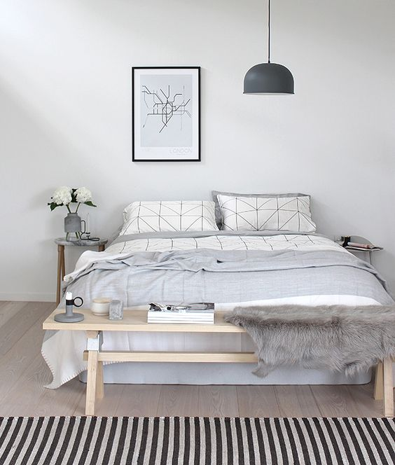 a casual Nordic bedroom in off-whites, with a wooden bench, a comfy bed and a pendant lamp for a modern look
