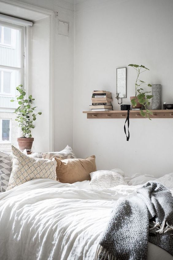 a charming bedroom with a bed, an open shelf, some greenery in pots and neutral bedding