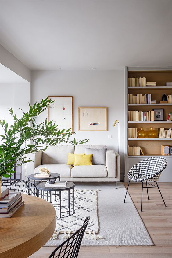a chic and neutral living room accessorized with yellow pillows and greenery to make it feel like spring