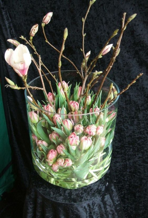 a chic flower arrangement of pink tulips and pink cherry blossom in a large jar