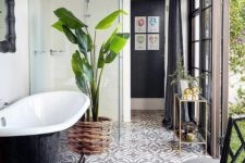 a chic monochromatic bathroom with a tile floor, a black tub and chair and a statement plant ina  wicker pot