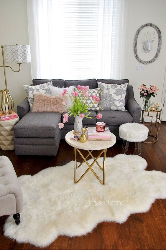 a chic spring living room with gold touches, neutral textiles, pink blooms and accents is a romantic and chic space