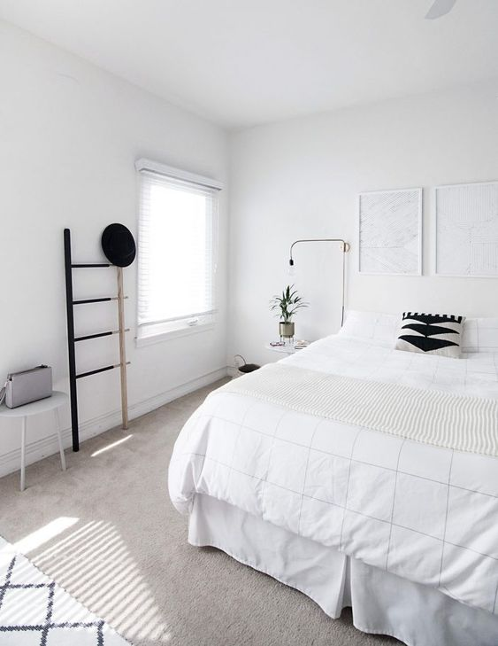 a clean Nordic bedroom with a white bed, artworks, a ladder, lamps and a stool - blakc for drama