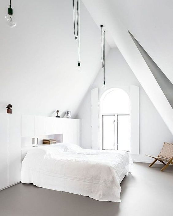a clean Nordic bedroom with an arched window, hanging bulbs, storage units, a bed and a wicker chair