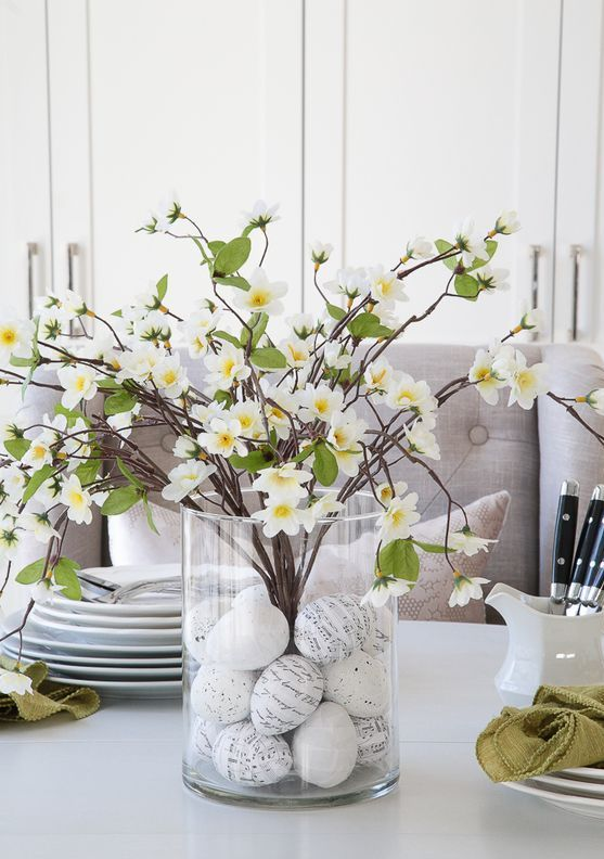 a clear vase with decorated Easter eggs and lush blooming branches is a cool and simple Easter centerpiece