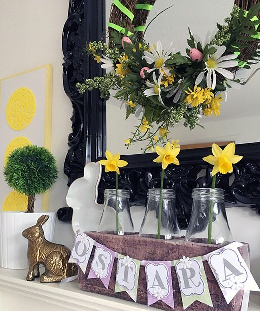 a colorful Easter mantel with bright daffodils and a wreath with blooms and greenery, bunnies and a bunting
