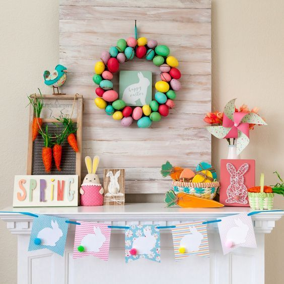 a colorful and fun Easter mantel with a bright egg wreath, a bunny bunting, a string art piece, some bunnies and a carrot garland