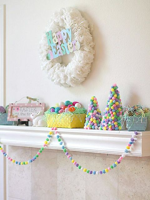 a colorful and fun Easter mantel with a coffee filter wreath and colorful letters, colorful pompom cones, colorful eggs and a garland