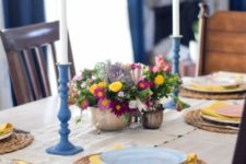 a colorful spring table setting with a bright floral centerpiece, wicker chargers, blue candle holders, yellow napkins