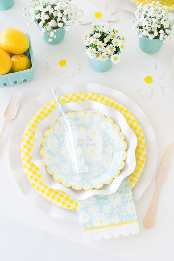 a colorful spring table setting with dairy and baby's breath centerpieces, yellow and white porcelain and touches of turquoise
