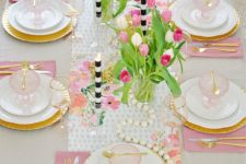 a colorful spring table setting with pink napkins, a floral table runner, wooden beads and striped candles plus pink glass