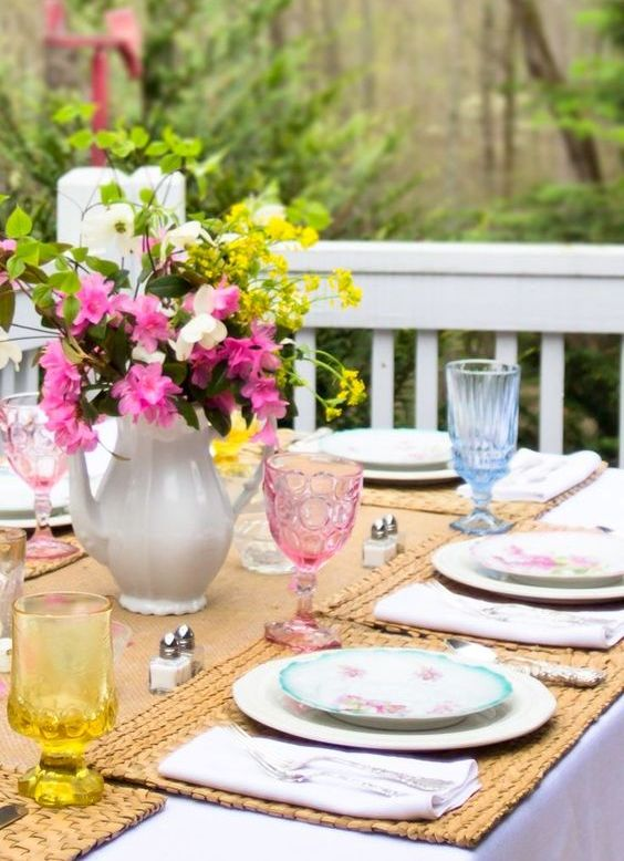 a colorful spring tablescape with bright glasses, a bright floral centerpiece, woven placemats and a runner