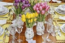 a colorful spring tablescape with bright yellow placemats, prited floral porcelain and lots of colorful tulips