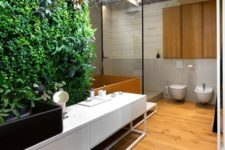 a contemporary bathroom with a living wall that is a statement here, it brings freshness and color to the space