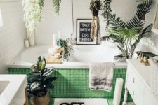 a contemporary bathroom with small tiles, lots of suspended planters with greenery and plants here and there