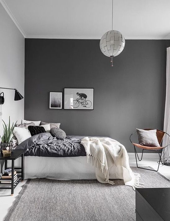 a contemporayr Scandinavian bedroom with a dark wall, monochromatic bedding, lamps and lights and a grey rug