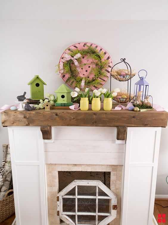 a cozy Easter mantel with green bird houses, yellow jars with blush tulips, faux eggs and nests and a pink basket with greenery