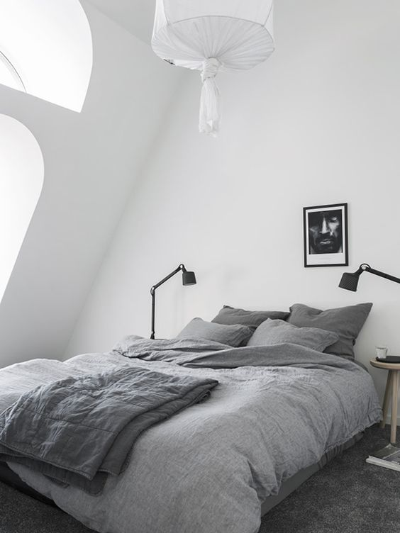 a cozy attic Nordic bedroom with arched windows, a bed, table lamps, an artwork and a pendant lamp