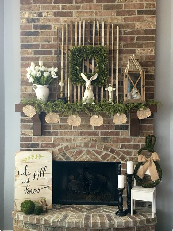 a cozy spring-inspired mantel with fresh greenery, a bunny ass garland, a bunny figurine and some white tulips in a jug