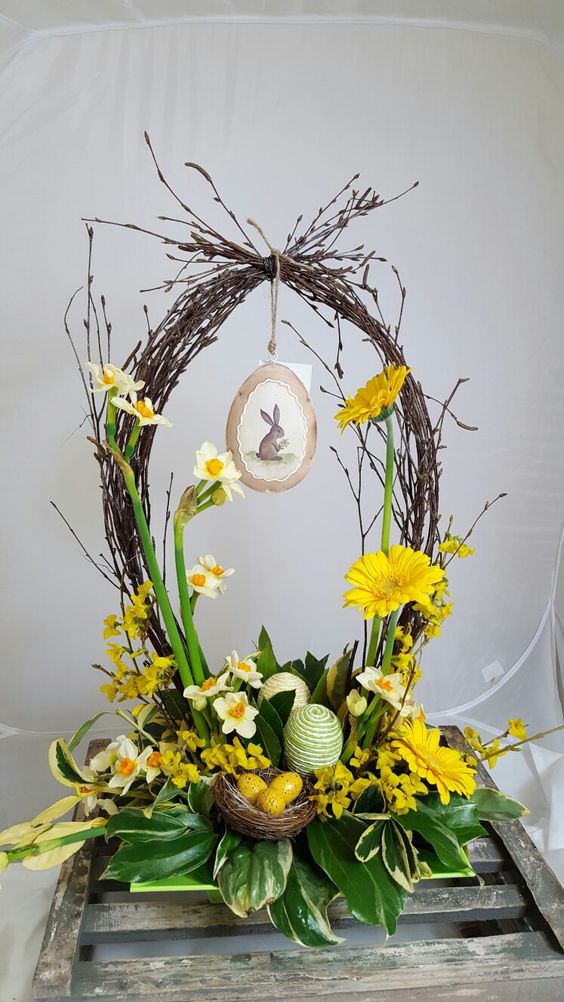 a cute Easter flower arrangement with a basket o vine, yellow blooms and foliage, some eggs and a nest with yellow eggs