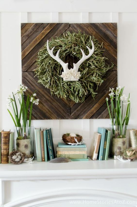 a cute spring mantel with a touch of wild, blooming bulbs, nests with fake eggs and a sign with antlers and a grass wreath