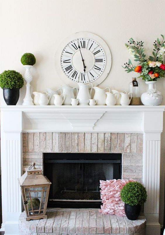 a farmhouse spring mantel with lots of vintage jugs, green topiaries, a moss ball in a lantern and a fresh flower arrangement