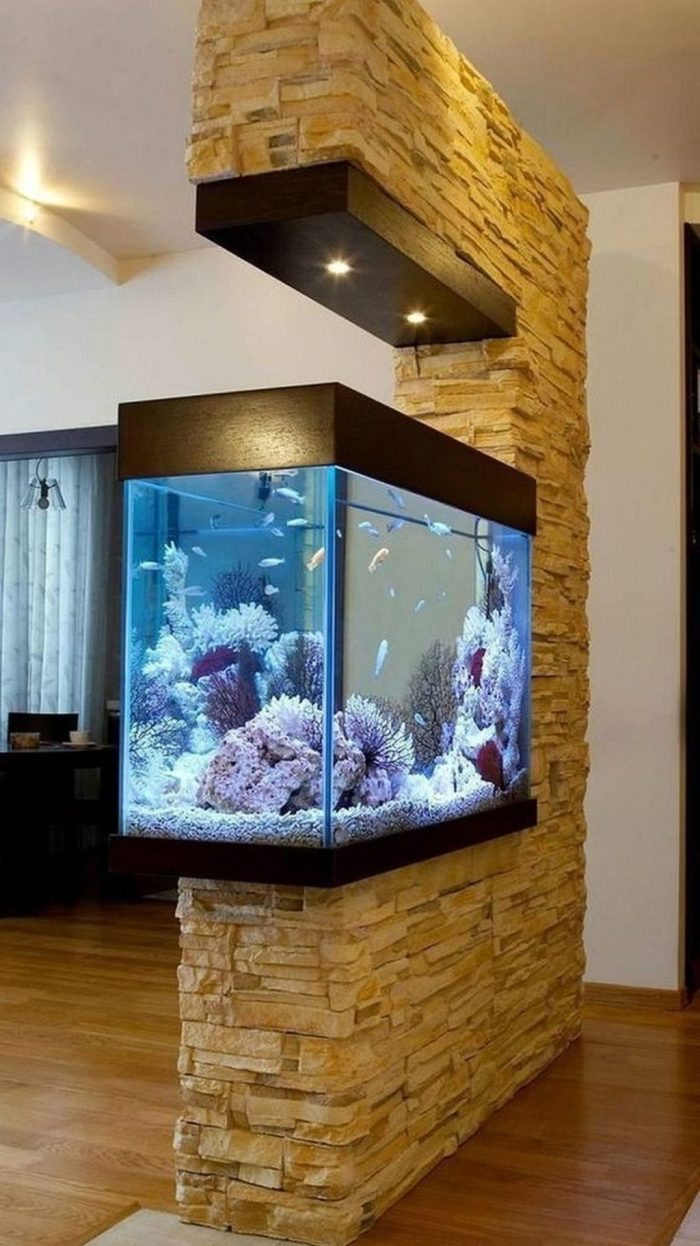 a faux stone wall with a built-in aquarium and lights is a bold modern space divider to go for