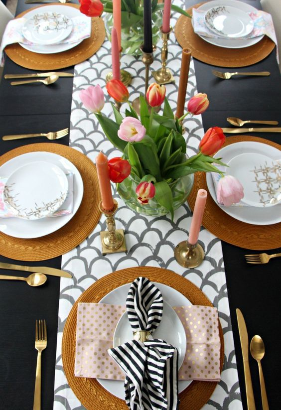 a fish scale runner, pink candles, a bright tulips centerpiece, wicker chargers and printed napkins