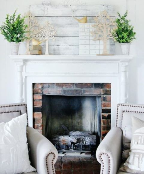 a fresh and inspiring mantel with potted greenery and cardboard trees plus some birdies