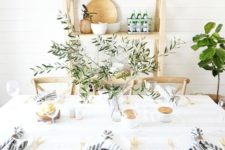 a fresh farmhouse tablescape with striped napkins, an olive branch centerpiece and gold cutlery