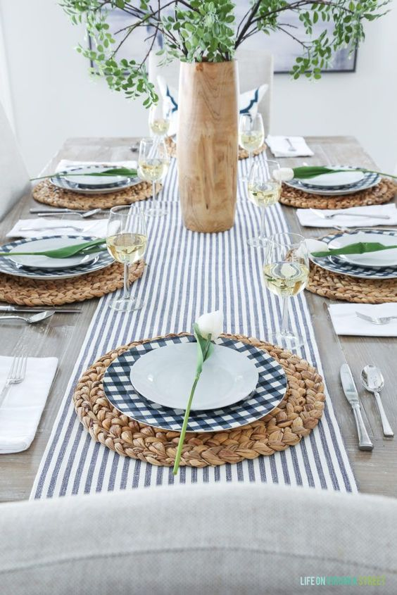a fresh modern spring table setting with a striped table runner, checked plates, wicker chargers, greenery and white tulips