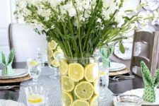 a fresh modern spring tablescape with a white floral centerpiece with lemon slices, wicker chargers, printed bunny napkins