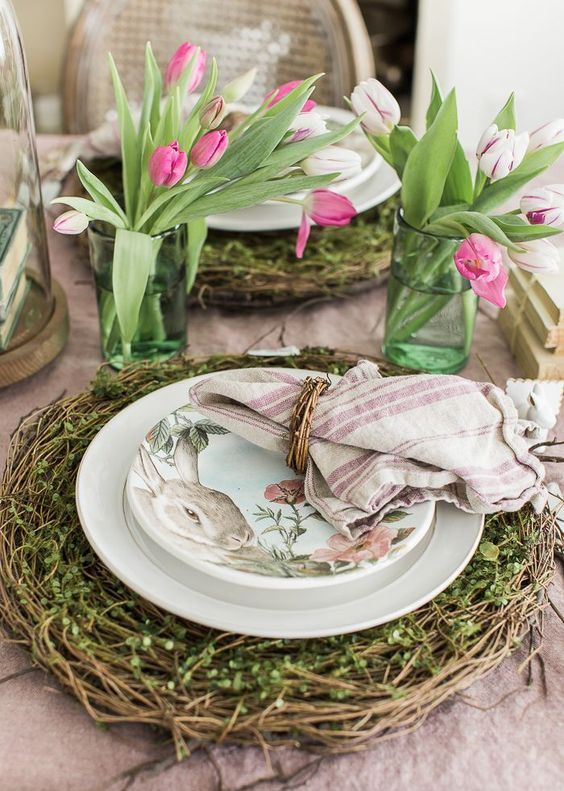 a fresh spring place setting with a vine and greenery charger, bunny printed plates, a striped napkin and tulip centerpieces