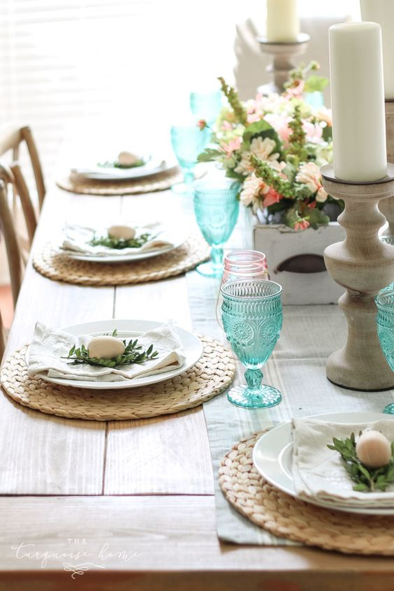 a fresh spring table with wicker chargers, blue and pink glasses, little eggs and greenery plus a lush centerpiece