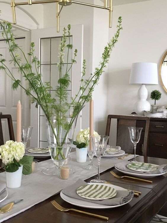 a fresh spring tablescape in green and cremay, with branches, hydrangeas and striped plates