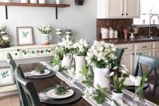 a fresh spring tablescape with a striped table runner, black matte chargers, white porcelain and white tulips centerpieces